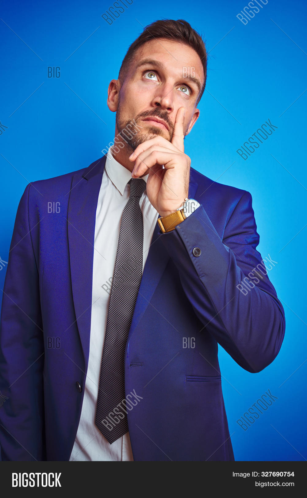 Vertical angle picture of young handsome business man over blue isolated background with hand on chin thinking about question, pensive expression. Smiling with thoughtful face. Doubt concept.