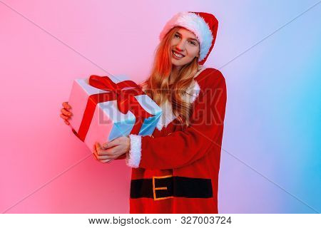 Happy Girl In Santa Hat Holding Big Gift Box Isolated On Background