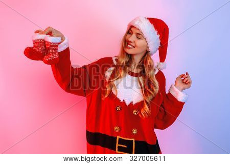 Happy Young Woman Wearing Santa Hat Holding Small Christmas Booties Standing On Background