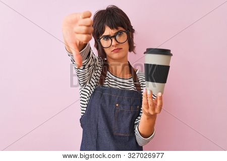 Young beautiful barista woman wearing glasses holding coffee over isolated pink background with angry face, negative sign showing dislike with thumbs down, rejection concept
