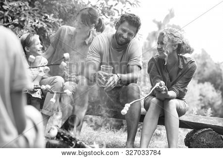 Black and white photo of Happy family sitting with woman while roasting marshmallows over burning campfire at park