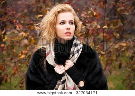 Russian girl. Portrait of beautiful young blonde woman in neckerchief, autumn park outdoors