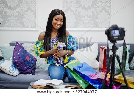 Cute African American Woman Making A Video For Her Blog With Money Using A Tripod Mounted Digital Ca