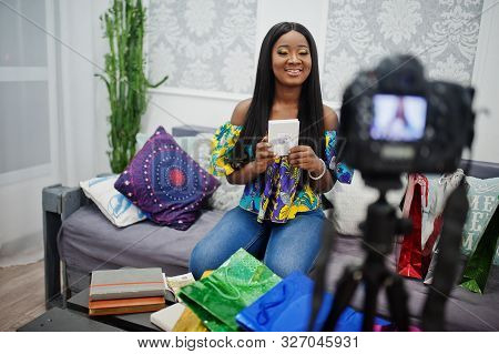 Cute African American Woman Making A Video For Her Blog Using A Tripod Mounted Digital Camera. Young