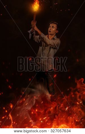 A full length portrait of a young goodlooking guy with the torch. Men casual fashion, revolution, uprising.