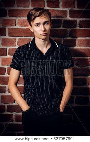 A portrait of a young goodlooking guy in a black t-shirt over the brick wall. Beauty of men, casual fashion.