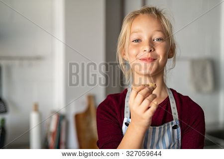 Funny little girl eating handmade cookie and looking at camera. Beautiful smart child holding a freshly baked biscuit. Little girl eating a chocolate cookie and looking with a funny expression.