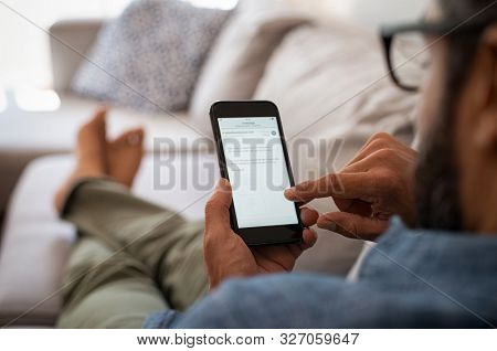 Closeup of a man hand holding cellphone with internet browser on screen. Man with spectacles relaxing sitting on couch. Closeup of mature latin man using smartphone to checking email at home.