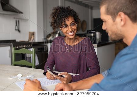 Young multiethnic couple doing accounting online with a phone bank app. Portrait of african casual girl sitting on table at home and analyzing home finance with documents.