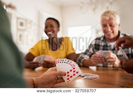 Closeup of woman hand holding playing cards. Group of mature friends relaxing and playing cards together. Senior people and african woman enjoying playing a game at home while sitting on wooden table.