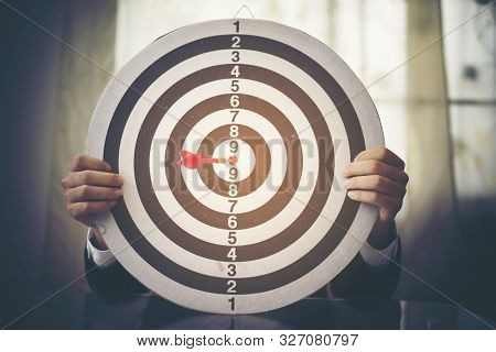 Businessman Holding Dartboard With Dart Arrow Hit In Target Center Of Dartboard, Successful Business