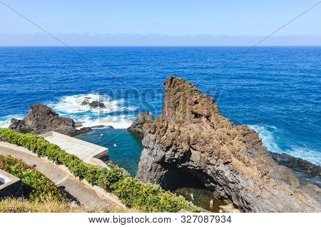 People Swimming In Natural Swimming Pools In The Atlantic Ocean In Seixal, Madeira Island, Portugal.