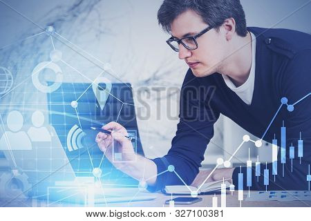 Young Market Analyst In Casual Clothes And Glasses Working With Digital Business Interface In Blurry