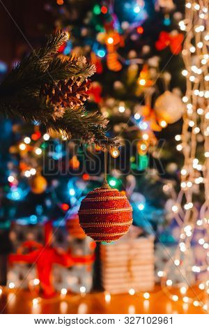 Christmas Ball Hangs On A Decorated Fir Tree Against The Background Of Burning Bokeh Lights At Night