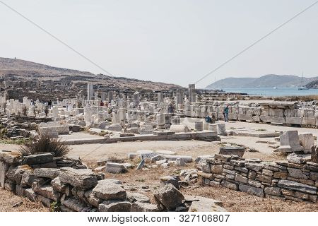 Delos, Greece - September 20, 2019: People Walk By Columns And Ruins On The Sacred Way On The Island