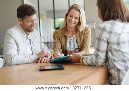 Couple meeting real-estate agent in office