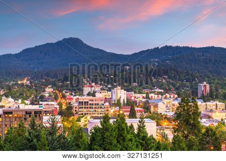 Eugene, Oregon, USA downtown cityscape and mountains at dusk.