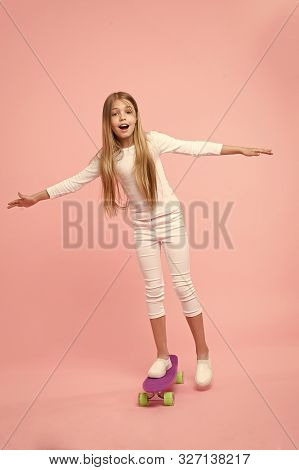 Regenerating Her Energy Skateboarding. Adorable Little Child Performing Skateboarding Tricks On Pink