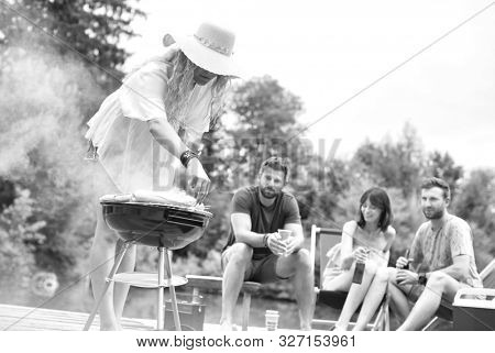 Black and white photo of Woman preparing food in barbecue grill with friends on pier