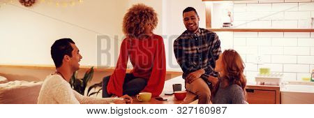 Side view of a group of happy young adult multi-ethnic male and female friends socialising sitting in the kitchen of an apartment, laughing together