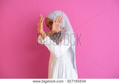 Young african american muslim woman wearing traditional Islamic clothes and showing two hands stop gesture against vilolence