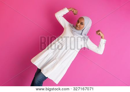 young afro beauty wearing traditional islamic clothes on plastic pink background  gender strenght