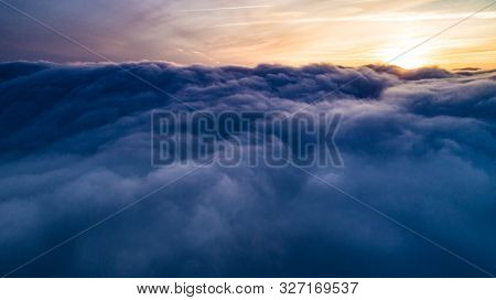 Aerial View Of Magical Blue Cumulus Clouds Settled In The Sky At Sunset. Winter Snow Leaden Clouds A