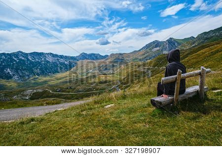 Woman On Wooden Bench Is Looking At Picturesque Summer Mountain Landscape Of Durmitor National Park,