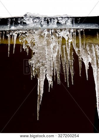 Icicles And Snow On Roof Closeup. Winter Weather Concept. Froze And Ice Background. Snow And Icicle.