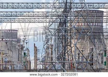 Electrical Sub Station Against The Cooling Towers Of A Power Plant. Electricity Generation Concept.