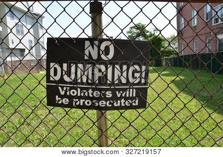 No Dumping Violaters Will Be Prosecuted Sign On Metal Fence