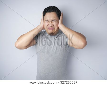 Young Asian Man Covering His Ear Ignoring Noise. Stressed Under Pressure Concept