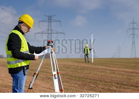 Land surveyors on construction site reading plans wear reflective clothing