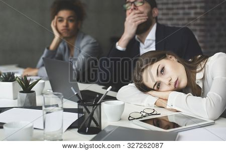 Boring Presentation. Young Business People Looking Bored, Woman Lying On Table And Looking Away