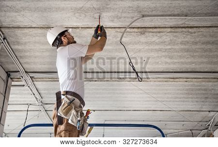 Electrician Installer With A Tool In His Hands, Working With Cable On The Construction Site. Repair