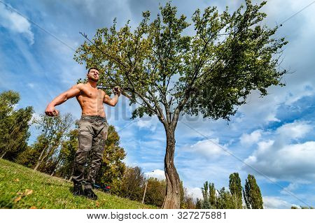 Handsome Muscular Shirtless Hunk Man Outdoor In Outdoor Setting. Showing Healthy Body. Halfnaked Spo