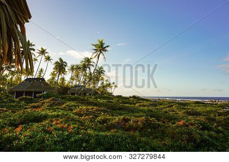 The Sun Sets Behind A Row Of Bungalows Facing The Pacific Ocean At Pension Raimiti On The Island Of