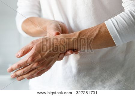 Closeup Of Male Arms Holding Her Painful Wrist Caused By Prolonged Work On The Computer, Laptop. Car