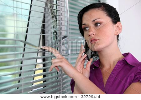 Woman peeking though window blinds