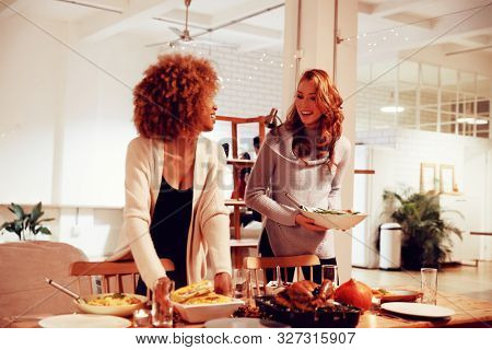 Front view of a young mixed race woman and a young Caucasian woman setting the table for Thanksgiving dinner with dishes of food in the dining room at home