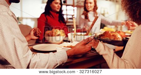 Over the shoulder view of a group of young adult multi-ethnic male and female friends sitting around a table holding hands saying grace before eating Thanksgiving dinner at home together