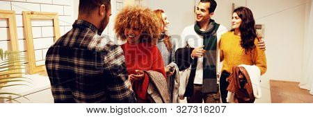 Front view of a group of young adult multi-ethnic male and female friends socialising, arriving at a party