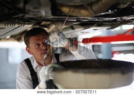 Portrait Of Male Standing In Garage And Examining Modern Automobile Underneath Pipes With Pouring Oi