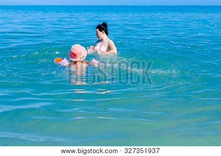 Happy Laughing Child Girl Is Playing With Her Mommy In Sea Water, Splashes And Learn To Swim With Co