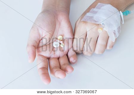 Hand Of Sick Woman Holding Pill And Iv Solution In Hospital Room.