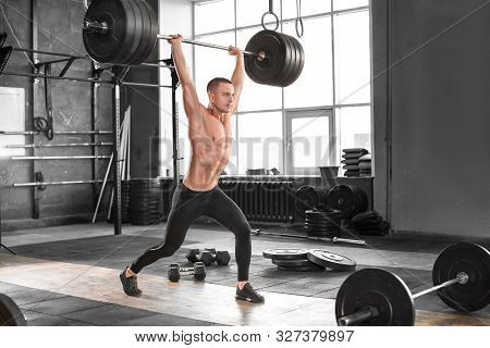 Man Train With Heavy Barbell Raised Over Head With A Bar In Gym. Fitness Gym Heavy Weight Lifting Ba