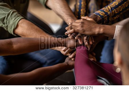 Cropped Close Of Diverse Businesspeople Putting Their Hands On Top Of Each Other Wearing Casual Clot