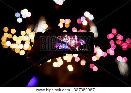 Silhouette Of Hands With Mobile Cell Phone To Take A Photo Of Fireworks.