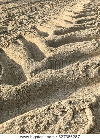 Tractor Tracks In The Sand On A Beach.