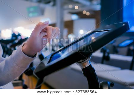 Woman Hand Using Touchscreen Display Of Interactive Floor Standing Black Tablet Kiosk At Exhibition
